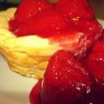 Ein kleiner Käsekuchen aus der Muffinform mit fruchtiger Erdbeersoße